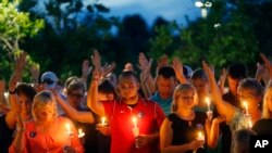 巴吞鲁日治愈之地大教堂前,为遇害警官举行烛光守夜仪式上,人们举起手进行祷告。(星期一,2016年7月18日)
