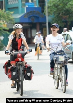 Vicky Wiesenmaier chats with a Vietnamese woman during a ride in Hanoi.