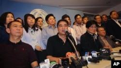 Pemimpin Partai Demokrat dan mantan Perdana Menteri Thailand Abhisit Vejjajiva (tengah) didampingi oleh para anggota partai saat berbicara dengan wartawan di Bangkok (8/12). (AP/Sakchai Lalit)