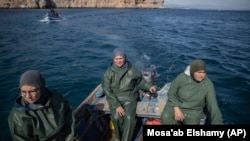 In this Feb. 12, 2020 photo, Fatiha Naji, right, Fatima Mekhnas, center, and Saida Fetouh, left, members of the first Moroccan female fishing cooperative go out to sea in a fishing boat on the coast of the Mediterranean, northern Morocco. (AP Photo/Mosa'ab Elshamy)