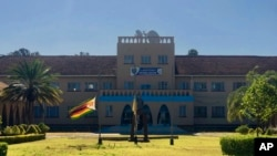 The Zimbabwean flag flies at half mast at Kutama College, a school where former Zimbabwean President Robert Mugabe studied in his rural home in Zvimba about 100 kilometres north west of the capital Harare, Friday, Sept, 27, 2019.