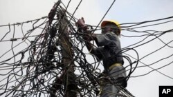A worker of Nigeria Power works on power lines in Nigeria.
