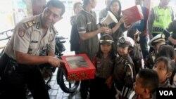 """Para """"polisi anak"""" dari TK Hompimpah Surabaya mendatangi kantor Polsek Tegalsari Surabaya, untuk mengenal profesi polisi sekaligus belajar berperilaku baik dan tidak melanggar hukum (foto: VOA/Petrus Riski)"""