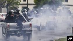 En esta imagen de archivo, tomada el 28 de mayo de 2018, policías con equipos antimotines, montados en la parte trasera de varias camionetas, disparan contra estudiantes universitarios que protestan contra el presidente de Nicaragua, Daniel Ortega, en Managua. (AP Foto / Esteban Félix, archivo)