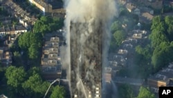 In this photo taken from video, smoke rises from a high-rise apartment building on fire in London, June 14, 2017.