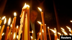 FILE - A man lights candles during a religious service marking the anniversary of mass killings of Armenians in Ottoman Empire in 1915 at an Armenian church in Tbilisi, Georgia.