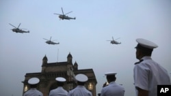 FILE - Indian navy personnel display their skills during a rehearsal for Naval Day celebrations near the Gateway of India monument in Mumbai, India, Dec. 1, 2019.