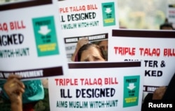 """FILE - Muslim women hold placards during a protest against a bill passed by India's lower house of Parliament last week that aims at prosecuting Muslim men who divorce their wives through the """"triple talaq,"""" or instant divorce, in New Delhi, Jan. 4, 2018."""