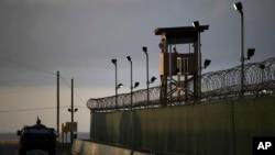 Seorang tentara AS berdiri di atap kendaraannya dengan membawa dengan senapan mesin (kiri), sementara seorang penjaga mengamati sekitarnya dari sebuah menara di penjara Teluk Guantanamo, Kuba (Foto: dok).