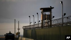 FILE - A U.S. soldier stands in the turret of a vehicle with a machine gun, left, as a guard looks out from a tower at the Guantanamo Bay prison in Cuba, March 30, 2010.