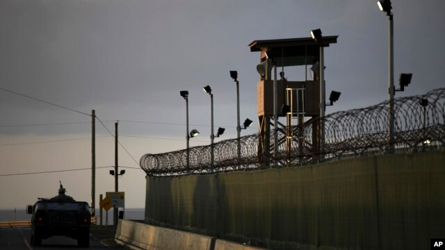 FILE -  A U.S. soldier stands in the turret of a vehicle with a machine gun, left, as a guard looks on from a tower at the Guantanamo Bay prison in Cuba.