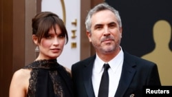 "Mexican director Alfonso Cuaron, best director nominee for his film ""Gravity,"" and his partner Sheherazade Goldsmith arrive at the 86th Academy Awards in Hollywood, California, March 2, 2014."