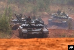 FILE - Russian tanks advance during the Zapad 2017 military exercises near St. Petersburg, Russia, Sept. 18, 2017.