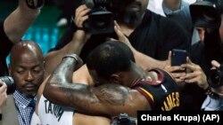 Košarkaš Klivlend Lebron Džejms grli rukija Bostona Džejsona Tejtuma na kraju sedme utakmcie finala Istočne konferencije u Bostonu, 27. maja 2018. (Foto: AP/Charles Krupa))