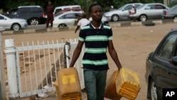Un homme porte des bidons d'essence à Abuja, Nigeria, le 26 mai 2015.