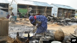 A woman salvages cooking pots at the site of an explosion in Maiduguri, Nigeria, June 8, 2017. Authorities in northeast Nigeria say at least 14 people are dead and dozens are wounded after Boko Haram militants launched a series of attacks.