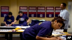 Denise Villagomez, a union member, writes on a sign as she and other volunteers prepare for Wednesday's immigration reform rally at the Service Employees International Union, which is co-organizing the event, in Washington, April 9, 2013.