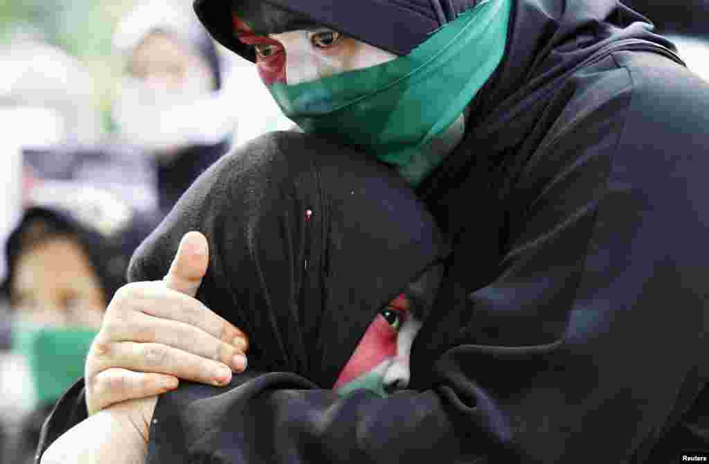 A Filipino Muslim woman, with colors of Palestinian flag painted on her face, cries as she embraces her child during a rally held by the Anak Mindanao (Children of Mindanao) Party List group outside the Israeli embassy in Taguig, Metro Manila, Philippines.