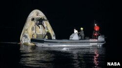 Support teams work around the SpaceX Crew Dragon Resilience spacecraft shortly after it landed with NASA astronauts Mike Hopkins, Shannon Walker, and Victor Glover, and Japan Aerospace Exploration Agency (JAXA) astronaut Soichi Noguchi aboard in the Gulf