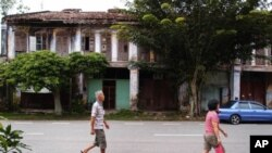 Papan residents strolling past a row of pre-war shop houses that are now mainly abandoned.