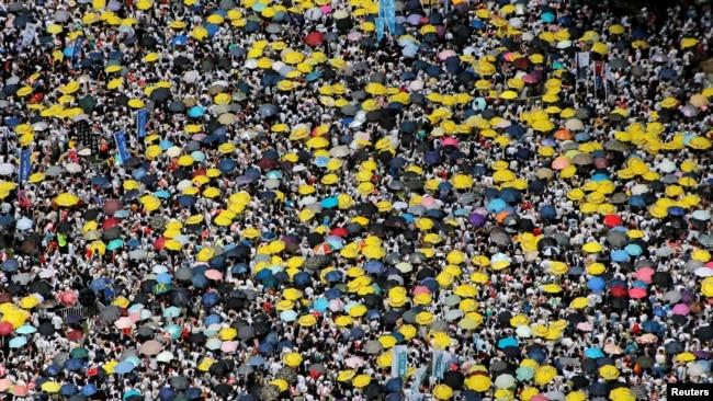 香港示威群眾要求當局廢除擬議中的允許把嫌疑人引渡到中國的《逃犯條例》修訂案。 他們手持黃色遮陽傘,這是過去的佔領中環運動的象徵。 (2019年6月9日)