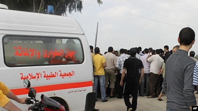 Lebanese civil defense ambulance, civilians gather at site where a cameraman was shot near Wadi Khaled, April 9, 2012.