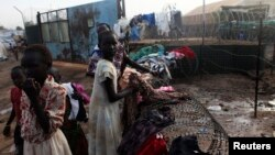 South Sudanese girls displaced by the fighting collect their laundry from a barbed wire in a camp for displaced persons in the UNMISS compound in Tongping in Juba February 19, 2014. Thousands of people have been killed and more than 800,000 have fled thei