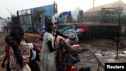 FILE - South Sudanese girls displaced by the fighting collect their laundry from a barbed wire in a camp for displaced persons in Juba, Feb. 19, 2014.