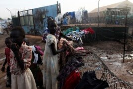 South Sudanese girls displaced by the fighting collect their laundry from a barbed wire in a camp for displaced persons in the UNMISS compound in Tongping in Juba, Feb. 19, 2014.