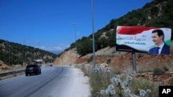"""In this Friday, July 20, 2018, photo, a poster of President Bashar Assad with Arabic that reads """"Welcome in victorious Syria."""" is seen on the border between Lebanon and Syria."""