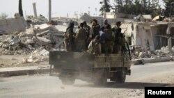 Des rebelles passent devant des bâtiments en ruine à al-Rai town, au nord d'Alep, Syrie, le 2 octobre 2016.