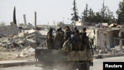 Des rebelles passent des bâtiments en ruine à al-Rai town, au nord d'Alep, Syrie, le 2 octobre 2016.