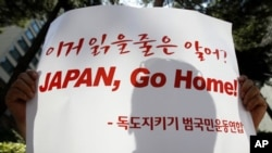 A protester holds a sign during an anti-Japan rally denouncing Japan's sovereignty claim on the Dokdo islets, or Takeshima in Japanese, in front of the Japanese embassy in Seoul, July 21, 2011