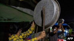 People clatter pans and tins to make noise to protest the military coup in response to a social media campaign in Yangon on February 2, 2021, as the party of Myanmar's toppled leader Aung San Suu Kyi demanded her immediate release Tuesday. (Photo by STR /