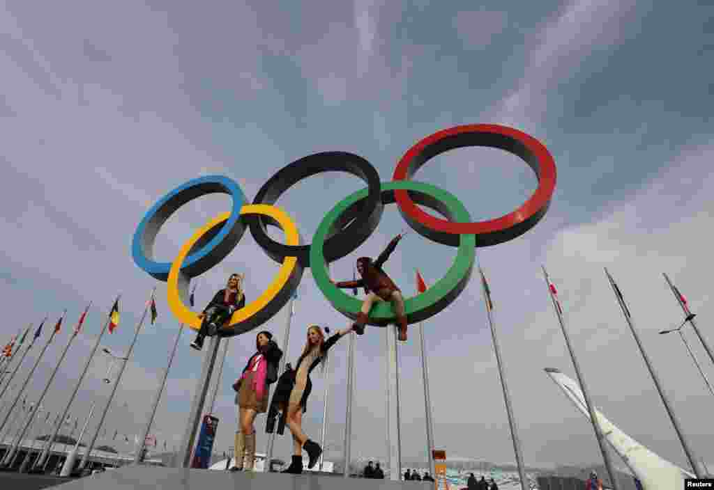 People pose for a picture with a set of Olympics rings at the Olympic Park a day after the closing ceremony for the 2014 Sochi Winter Olympics, Russia.