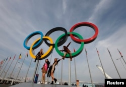 FILE - People pose with Olympics rings at the Olympic Park in Sochi, Russia, Feb. 24, 2014.
