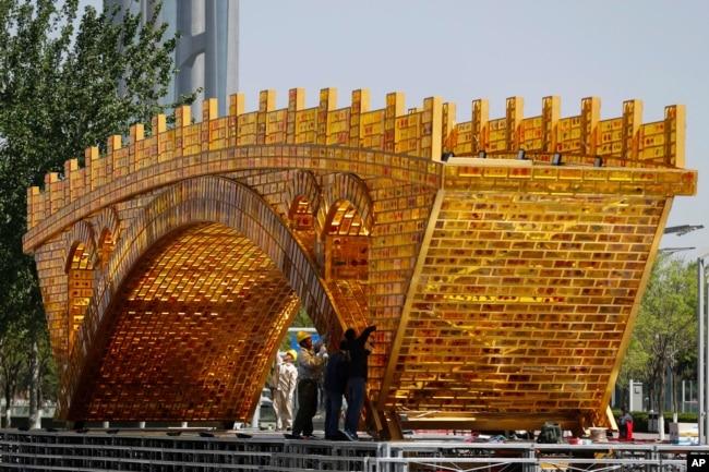 2017年4月18日,工人们在中国国家会议中心外头的平台上,为丝绸之路黄金大桥装置缆线。北京将于5月在国家会议中心举办一带一路峰会。
