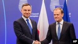 Poljski predsednik Andžej Duda rukuje se sa predsednikom Evropskog saveta, svojim zemljakom Donaldom Tuskom.