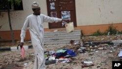 Un homme ramasse un objet appartenant à un étudiant après un attentat à la bombe à l'université de la cité de Zaria, Nigeria, le 7 juillet 2015.