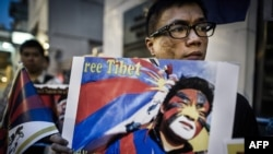 Rights group activists stage a protest to raise awareness on the human rights situation in Tibet and the closure of the territory to foreign visitors, outside the Chinese liaison office in Hong Kong, June 20, 2012.