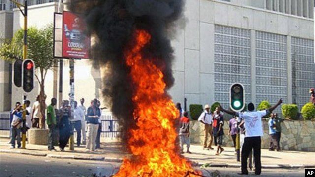 A man burns vegetation in the street after protesters went on a rampage after a court injunction stopped them from demonstrating against the economic and democratic crisis in the country, in Lilongwe, Malawi, July 20, 2011 (file photo)