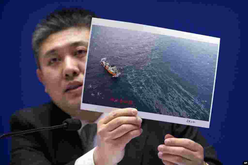中国国家海洋局生态与环境保护司副司长霍传林在新闻发布会上展示一艘救援船和海上浮油的照片。中国官员说,他们还在争论是否打捞上个月沉没的伊朗油轮桑吉号。