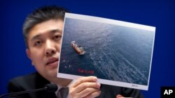 Huo Chuanlin, deputy director of the Department of Ecological and Environment Protection of China's State Oceanic Administration, holds a photo showing a rescue ship and an oil slick during a press conference about the Iranian oil tanker Sanchi, which exploded and sank after a collision in the East China Sea in January, at the Information Office of the Ministry of Transport in Beijing, Thursday, Feb. 1, 2018. Chinese officials say they are still debating whether to try to raise an Iranian oil tanker that sank last month with the loss of all 32 crew members.