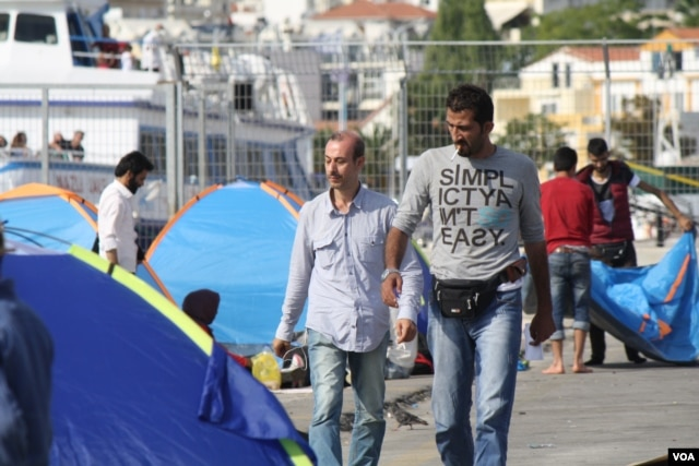 Refugees and other migrants arrive in Greek islands on dangerous boats before boarding a commercial ship to Athens. Those without enough money for the ship are left behind. (H. Murdock/VOA)