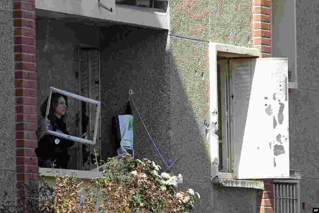 A police woman inspects the balcony of the apartment where special forces police staged the assault on the gunman Mohamed Merah, in Toulouse, March 23, 2012. (Reuters)
