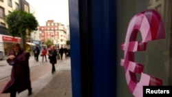FILE - A sign displaying the euro symbol is seen on a shop window in Dublin, Oct. 22, 2014.