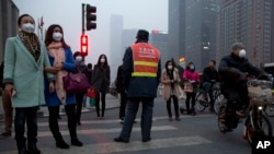 FILE - Pedestrians wearing mask against heavy pollution wait to cross a traffic junction in Beijing, China, March 16, 2015.