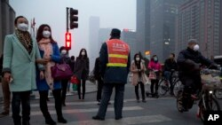 Pedestrians wearing masks wait in heavy pollution to cross traffic in Beijing, China, March 2015. (AP)