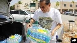 Ông Eduardo chất nước lên xe chuẩn bị trong trường hợp bão Isaac thổi vào Florida