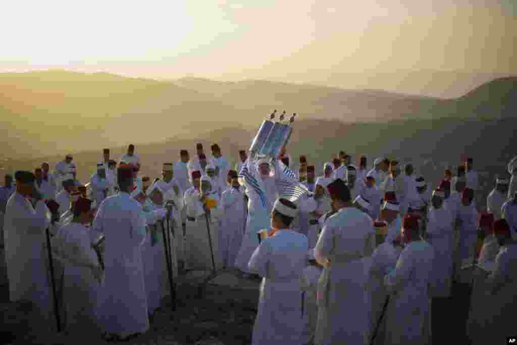 A member of the ancient Samaritan community holds up a Tora scroll as worshippers pray during the Passover pilgrimage at the religion's holiest site on the top Mt. Gerizim, near the West Bank town of Nablus.
